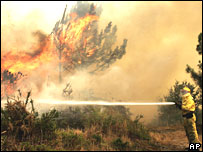 Firefigher spraying water onto one of the fires in north-west Spain