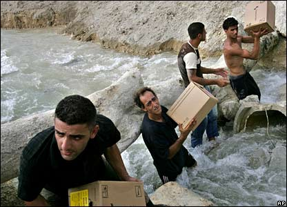 Aid workers transfer medical supplies intended for south Lebanon by hand across the Litani river on 7 August 2006