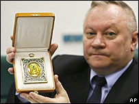 Russian culture ministry official Anatoly Vilkov shows recovered icon depicting Saint Serafim Sarovsky