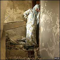 Badiaa Umm Hassan, a Lebanese woman, cries on the bloodstained stairs of her apartment in southern Beirut, destroyed on 7 August by an Israeli missile strike