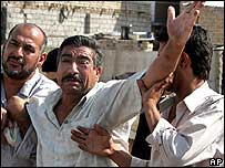 An Iraqi man grieves at the loss of his relative in a Baghdad bombing 08 Aug