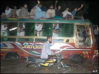 Passengers travel on the roof of a bus after rains hit Karachi