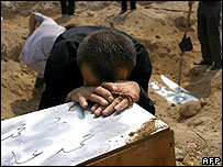 A Lebanese man cries over the coffin of his son at a mass grave in Tyre