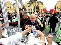 Personas prueban pisco peruano en una plaza pública