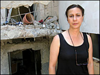 A resident of Kiryat Shmona in northern Israel stands in front of her missile-damaged apartment block