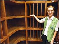 Assistant shows empty wine shelves at supermarket