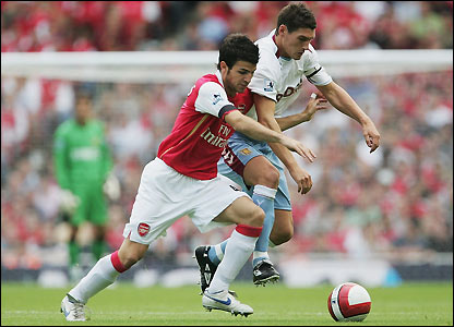 Cesc Fabregas holds off Gareth Barry