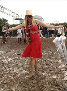 A woman in a red dress standing in mud