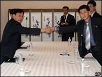 Lim Yong-hoon, chief of inter-Korean affairs at South Korea's Red Cross, left, shakes hands with his North Korean counterpart Pak Yong Il