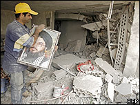 Man in ruined building with portrait of Hezbollah leader Hassan Nasrallah