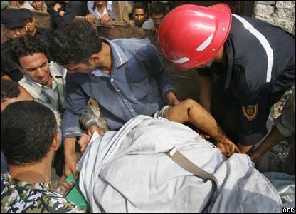 Egyptian rescue workers carry out a victim of the train collision in Qalyoub