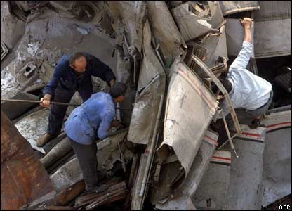 People struggle try to force their way through the wreckage to find survivors of the Egypt train collision
