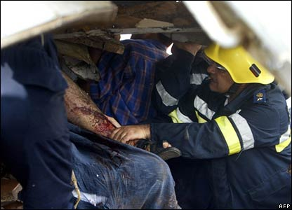 Rescue workers try to pull a victim from the wreckage of the train crash in Qalyoub