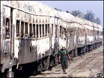 A rescue walks alongside burned out carriages - Egypt's worst train disaster in 2002