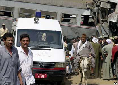 An ambulance is positioned alongside the wrecked carriages in Qalyoub