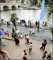People tango alongside the Seine