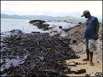 A Filipino man looks at oil-soaked debris on a beach on 22 August