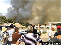 People watch as smoke engulfs houses in Kassandra, Northern Greece.