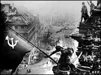 Soviet soldier raising the Red Flag over the Reichstag after Allied forces entered Berlin