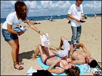 UMP activists distribute leaflets with flip-flops on a beach in Arcachon, south-western France