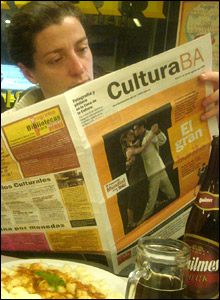 Woman reads a newspaper featuring the Tango World Championships on its front page
