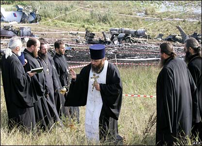 Orthodox priests perform a service at the crash site