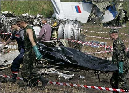 Workers remove a body from the crash site