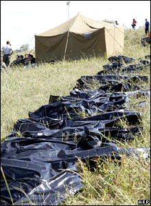 Body bags are lined up on the grass near the crash site