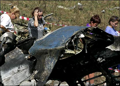 Local residents walk past wreckage of crashed plane with shocked looks