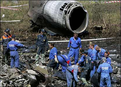 Workers sift through wreckage of the crashed plane