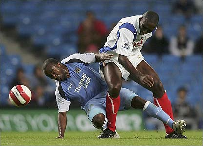Darius Vassell is challenged by Portsmouth's Sol Campbell