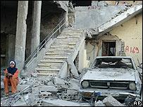 امرأة تجلس بين حطام بيتها في صريفة