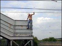 Man climbs onto wires