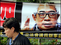 A woman walks past a billboard showing detained journalist Ching Cheong in Hong Kong