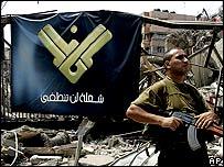 Militiaman guards Beirut headquarters of al-Manar TV after Israeli air raid