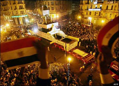 Excited Cairo crowd wave flags as the royal statue passes by