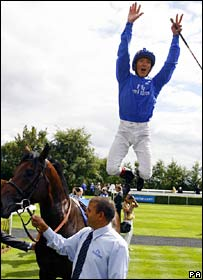 Frankie Dettori leaps off a horse after winning a race