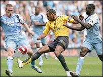 Thierry Henry (centre) is closely guarded by Richard Dunne (left) and Micah Richards (right)