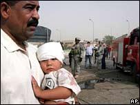 اب عراقي يحمل ابنته التي اصيبت  في انفجار اليوم ببغداد