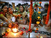 Women lighting candles during religious celebrations