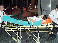 An unidentified woman is carried on a stretcher by paramedics