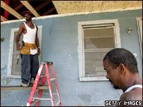 Dos hombres reparan una casa destruida por Katrina