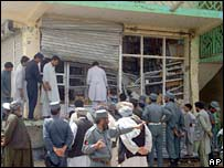 People look at the damage after a suicide attack at a market in Lashkar Gah