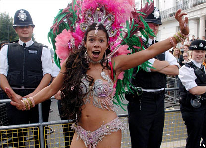 Dancer at Notting Hill Carnival in front of policeman