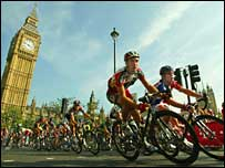 Cyclists pass the Houses of Parliament