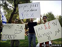 Israeli reservists hold signs demanding an investigation