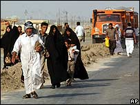 Local people flee Diwaniya on Monday following fierce fighting between Iraqi troops and Shia militiamen