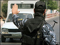 A Hamas-led government militia member stops a vehicle in southern Gaza