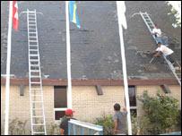Trabajadores en el techo de una casa (imagen cortesía del Proyecto Defensa Laboral)