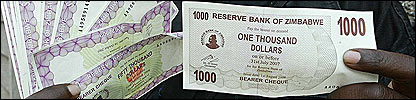 Zimbabwean displays a new banknote (R) alongside the phased out bearers cheques (L)